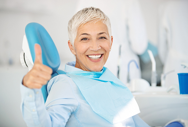 mature woman in dental chair with beautiful, straight teeth after using invisalign